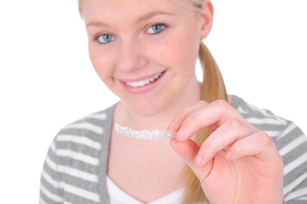 Teenage girl holding her clear aligner