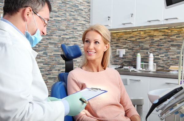 Woman talking to dentist during dental exam at McDonald DDS in Plano, TX