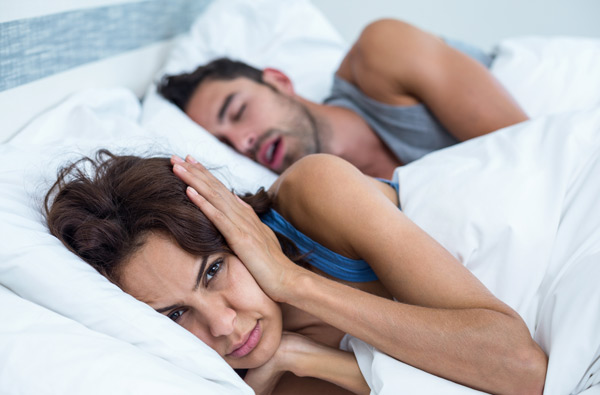 Woman covering ears while husband snores. Learn more about sleep apnea and oral appliances at McDonald DDS in Plano, TX